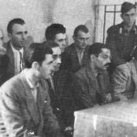 """Carlo De Sanctis (al centro, con baffi e occhiali) e la sua """"banda"""" durante il processo."""