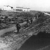 11 aprile 1945. Commandos della Marina Inglese marciano lungo gli argini meridionali delle valli attraverso le campagne allagate