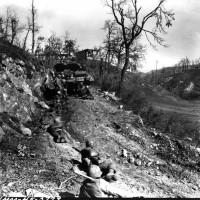 Genieri della 10° Divisione di Montagna riposano mell'ultima fila di un distruttore di carri che offre loro un po' di protezione dal fuoco dei franchi tiratori sulla strada durante l'assalto della 10° Divisione da Montagna della 5° Armata.
