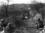 Un Mitragliere e due fucilieri della Compagnia K, 87° Fanteria di Montagna statunitense coprono una squadra di assalto che cerca di snidare i tedeschi asserragliati nella Casa Campolungo, vicino Passo Brasa (Castel d'Aiano).