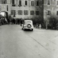"""Un'auto d'epoca si avvicina alle persone che sostano davanti alla porta della città. Si tratta di un """"evento"""": nella Soliera degli anni Trenta e della Seconda guerra mondiale il traffico dei veicoli civili a motore rimane infatti piuttosto limitato."""